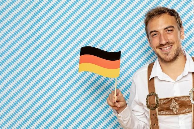 Мужчина держит немецкий флаг с копией пространства Бесплатные Фотографии