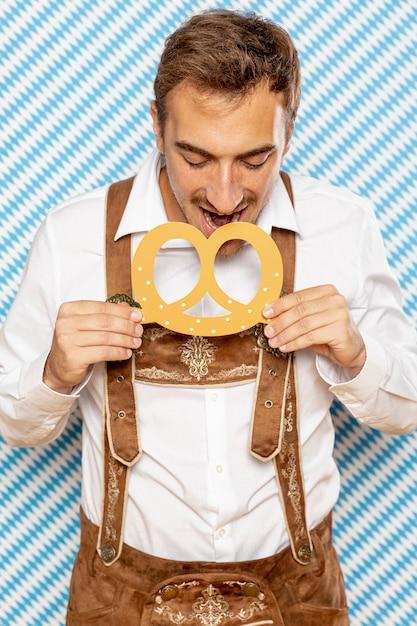 ドイツのプレッツェルを食べている男の正面図 無料写真