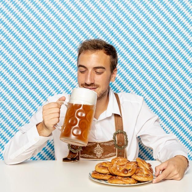 Мужчина пьет светлое пиво с рисунком фона Бесплатные Фотографии