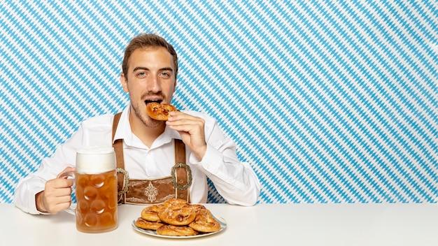 Человек ест немецкие крендели с копией пространства Бесплатные Фотографии