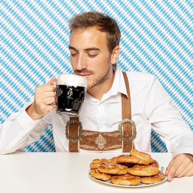 Вид спереди человека, пьющего черное пиво Бесплатные Фотографии