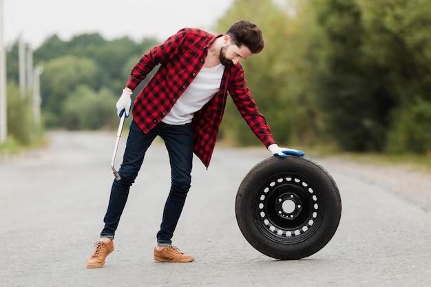 レンチとタイヤを持つ男のロングショット 無料写真