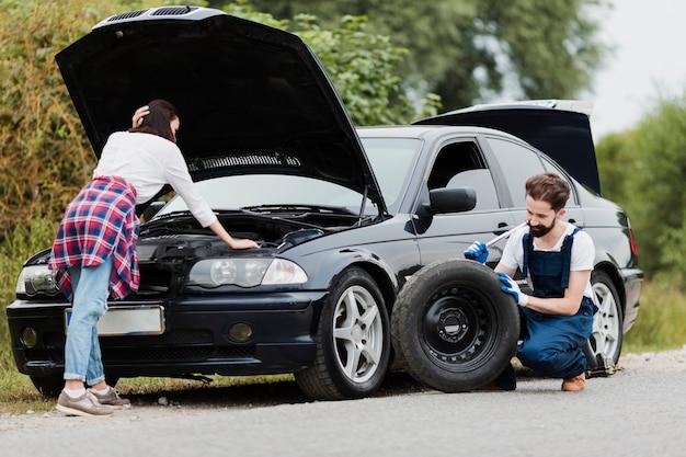 女性のエンジンとタイヤを変更する男をチェック 無料写真