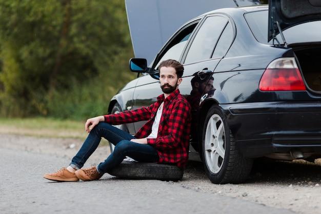 車にもたれて男の側面図 無料写真