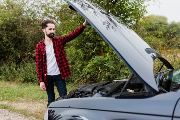 車のエンジンを見て男 無料写真