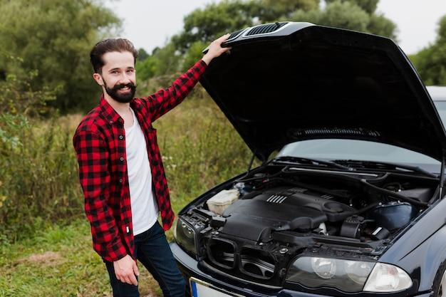 フランネルのシャツと車のボンネットを持つ男を開く 無料写真