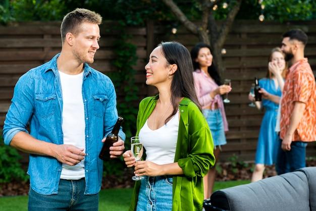 Очаровательные друзья смотрят друг на друга с напитками Бесплатные Фотографии
