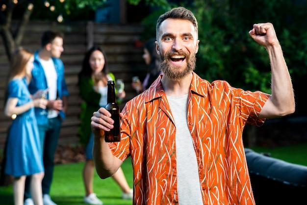 Вид спереди счастливый молодой человек, держащий пиво Бесплатные Фотографии