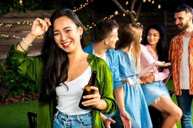 Улыбающаяся молодая девушка держит бутылку пива Бесплатные Фотографии