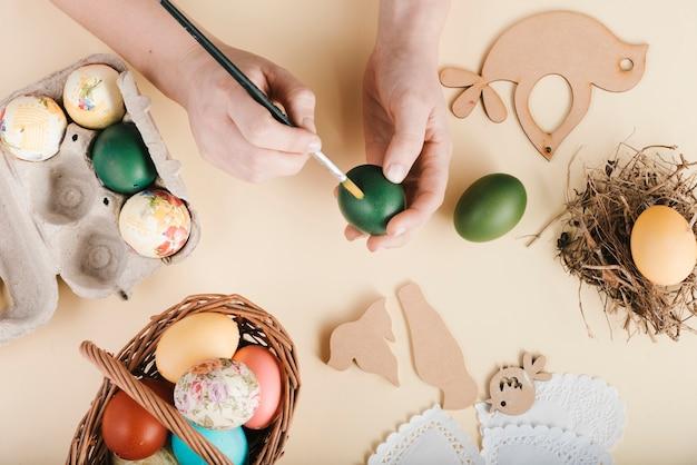 Вид сверху женщина, украшающая пасхальные яйца Бесплатные Фотографии