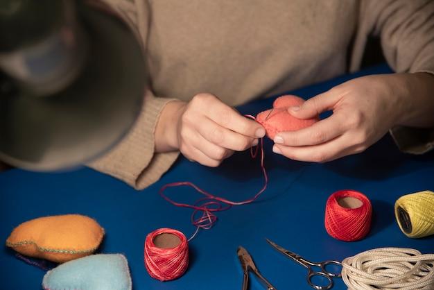 Крупным планом женщины шить плюшевые сердца Бесплатные Фотографии