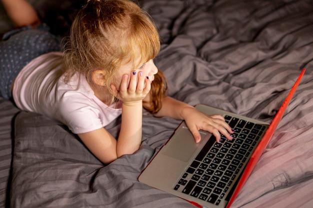 寝室のラップトップ上の高角度の女の子 無料写真