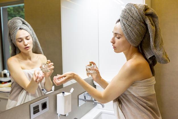 香水にしようとしているサイドビュー女性 無料写真