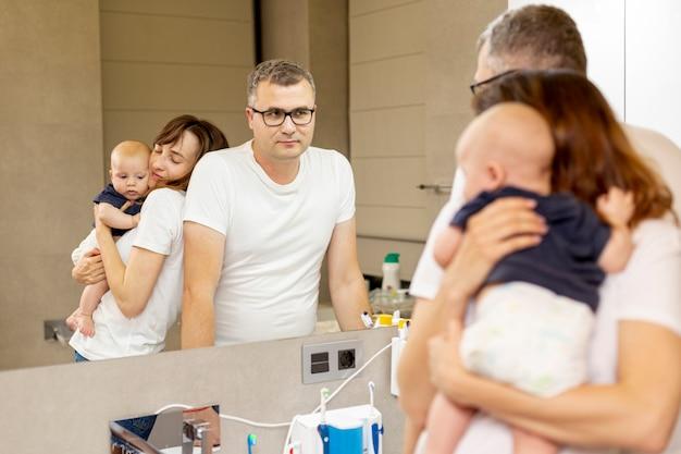 鏡を見てミディアムショット家族 無料写真