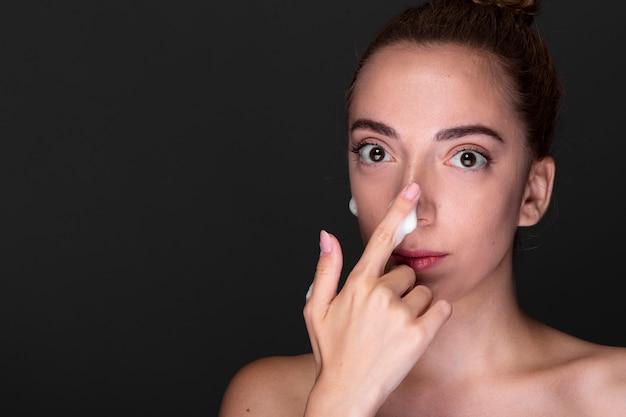 Молодая женщина, применяя крем для носа Бесплатные Фотографии