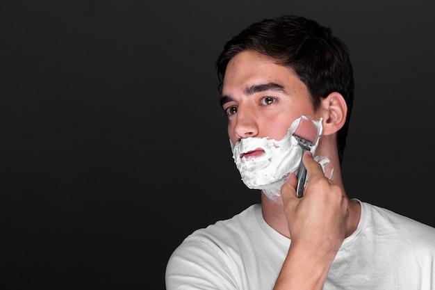 Мужчина бреет бороду бритвой Бесплатные Фотографии