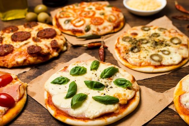 Крупный план мини-пиццы на деревянный стол Бесплатные Фотографии