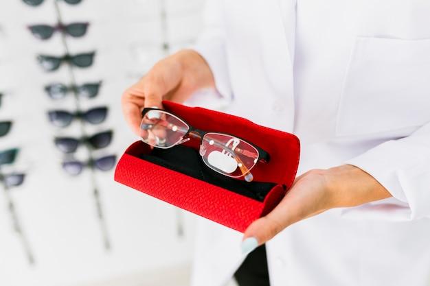 Женщина, держащая красный футляр и очки Бесплатные Фотографии