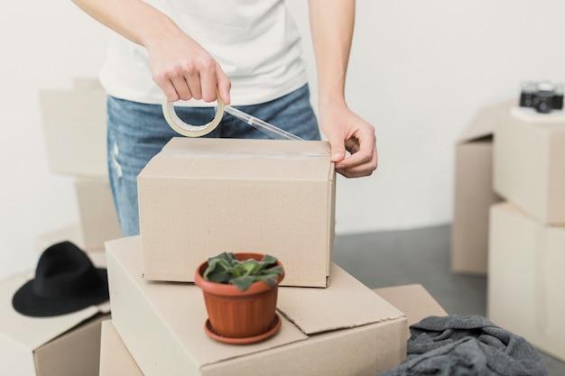 ボックスにチェロテープを置くクローズアップ男 無料写真