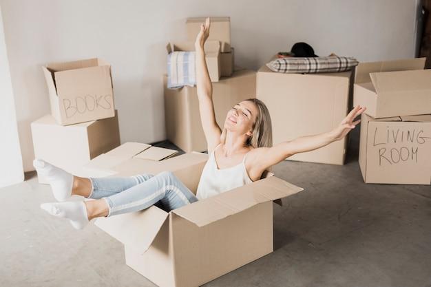 カートンボックスに座っている幸せな若い女 無料写真