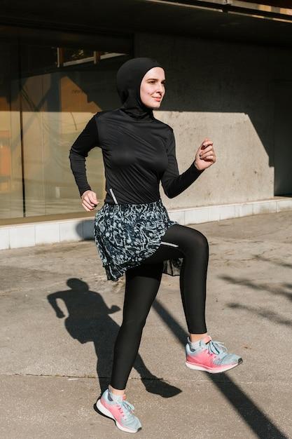 ヒジャーブトレーニングを持つ女性のフルショット 無料写真