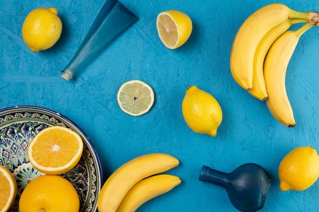 Чаша из лимонов и бананов на синем фоне Бесплатные Фотографии