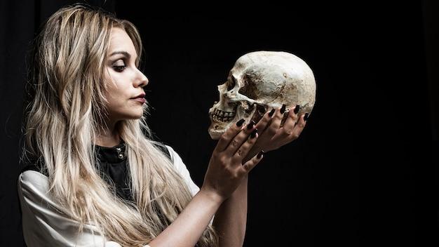 黒い背景に頭蓋骨を見ている女性 無料写真