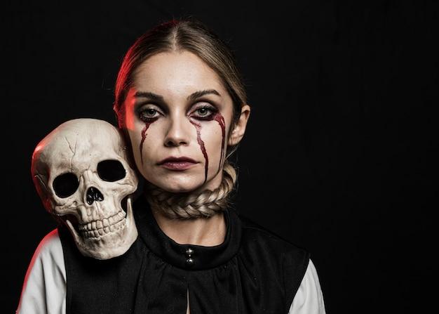 肩に頭蓋骨を保持している女性の正面図 無料写真
