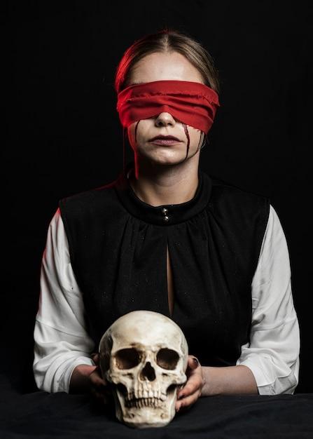 頭蓋骨を保持している赤い目隠しを持つ女性 無料写真