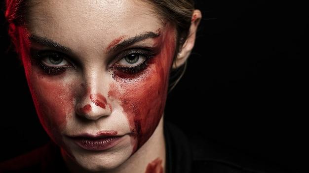 血まみれの化粧とコピースペースを持つ女性 無料写真