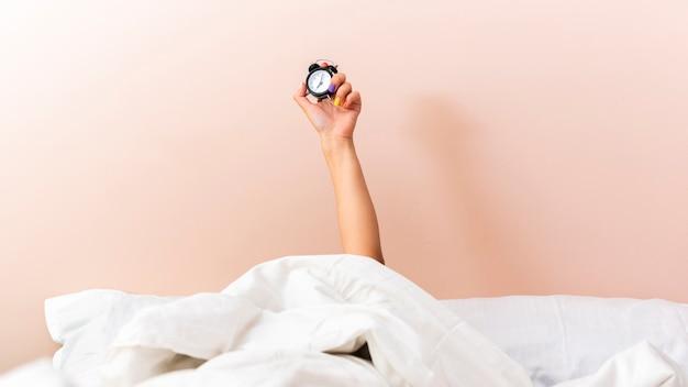 Женская рука поднимает часы из-под простыней Бесплатные Фотографии