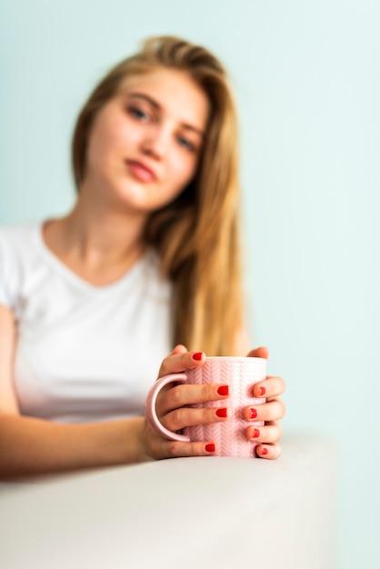 カメラ目線のカップを保持している女性 無料写真