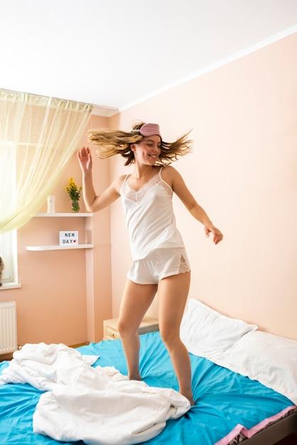 若い女性がベッドでジャンプ 無料写真
