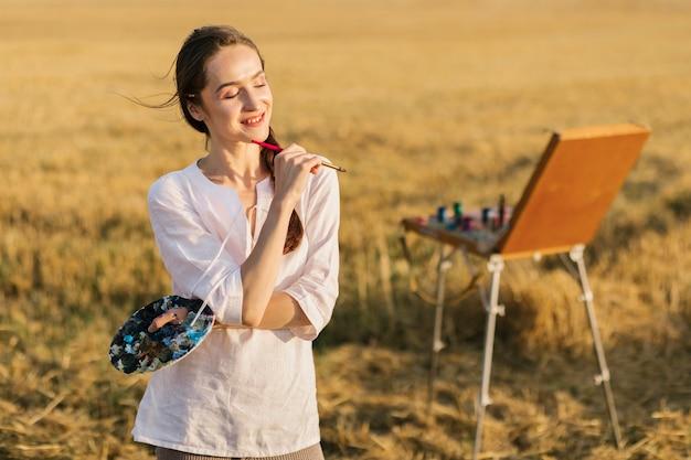 自然の中でインスピレーションを探している若い画家 無料写真