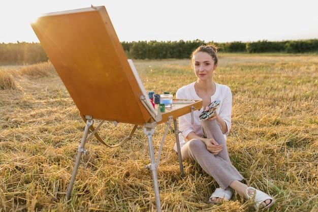 自然の中で座っている創造的な若い女性 無料写真