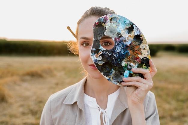 Творческая молодая женщина, держащая палитру живописи Бесплатные Фотографии
