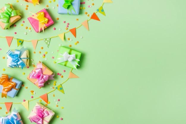 緑の背景を持つテーブルの上のトップビューカラフルなギフト 無料写真