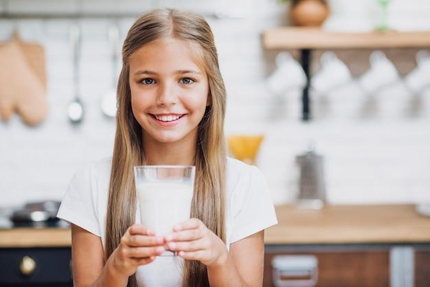 ミルクのガラスを保持しているスマイリーの女の子 無料写真