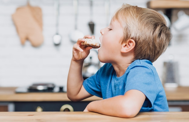 クッキーを食べてサイドビュー少年 無料写真