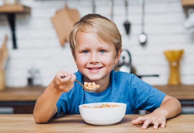 カメラを見ながら穀物を食べる少年 無料写真