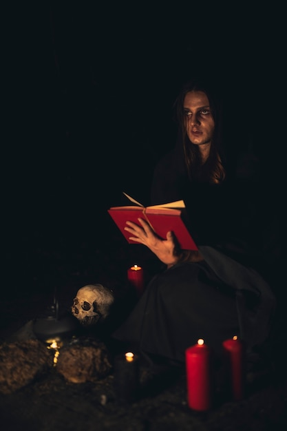 Человек читает красную книгу заклинаний в темноте Бесплатные Фотографии