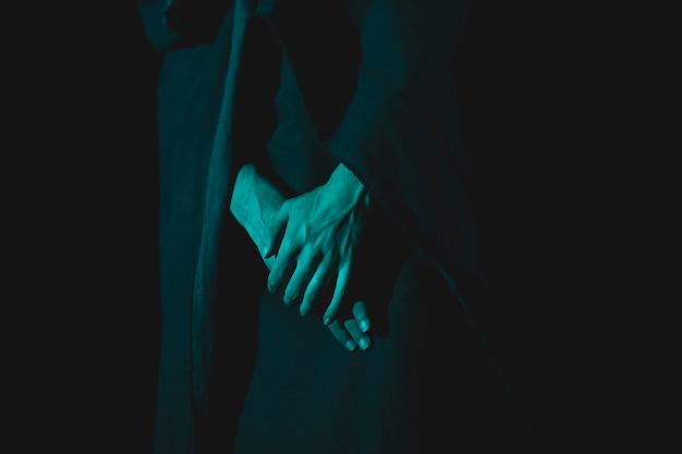 Крупный план руки, держащей вместе в темноте Бесплатные Фотографии