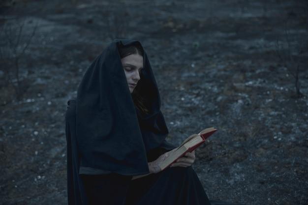 Человек читает книгу заклинаний снаружи Бесплатные Фотографии