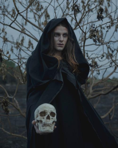 Мужской маг в черной одежде, глядя с черепом в руке Бесплатные Фотографии