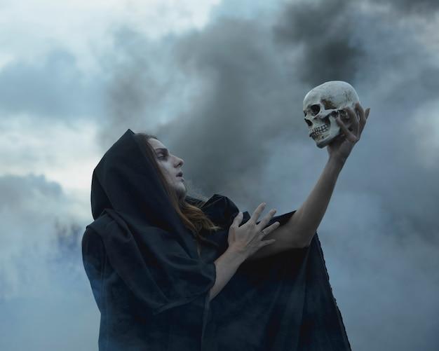 暗闇の中で頭蓋骨を押しながらそれを見て男 無料写真