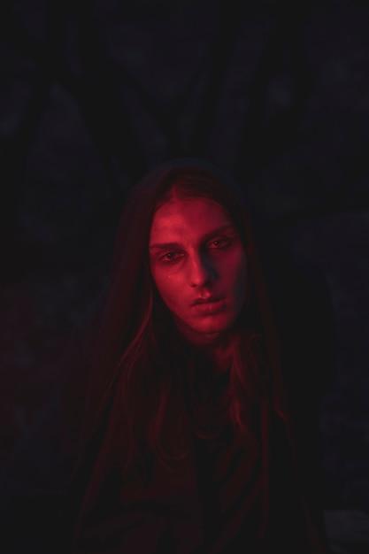 暗闇の中で座っている赤い光の色合いの男 無料写真