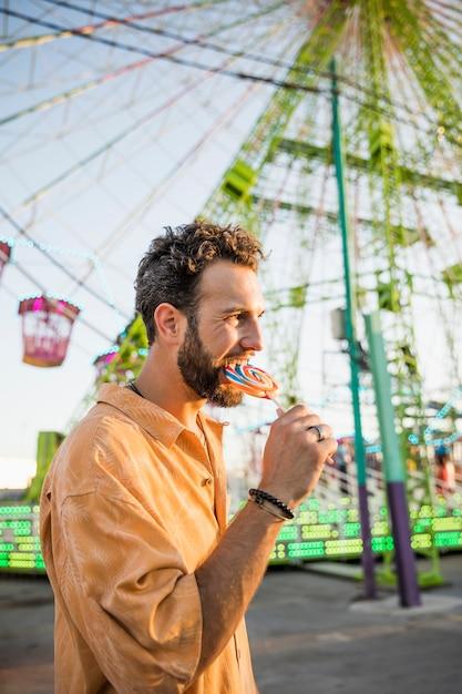 遊園地でロリポップを食べているハンサムな男 無料写真