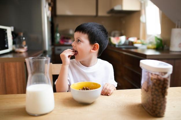 自宅で朝食を持っている小さな男の子 無料写真