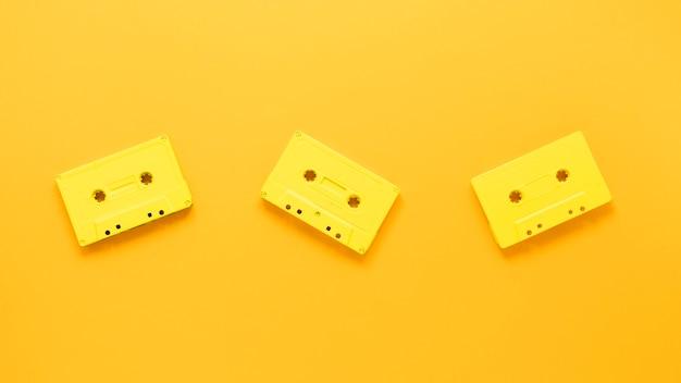 黄色の背景にカセットのフラットレイアウト 無料写真