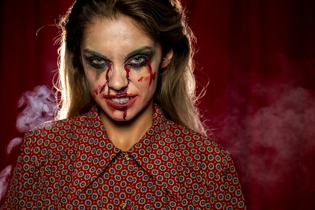 にやにや血のようなメイクを持つ女性 無料写真